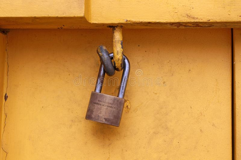 Close-up Old rusty padlock hanging on yellow wooden wall. stock image