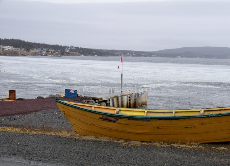 Yellow dory and the Trinity Bay, NL Canada. View past a yellow fishing dory towards the bay; early Spring landscapes along the Baccalieu trail, Avalon Peninsula stock photos