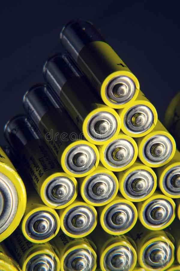 Yellow double A batteries reflecting in mirror, electricity storage concept. Filtered photo - stack of yellow AA batteries reflecting in mirror close up stock images