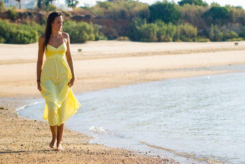 Yellow dress stroll on beach stock photography