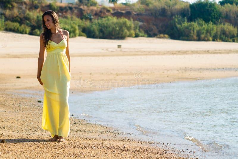 Yellow dress stroll on beach royalty free stock photos