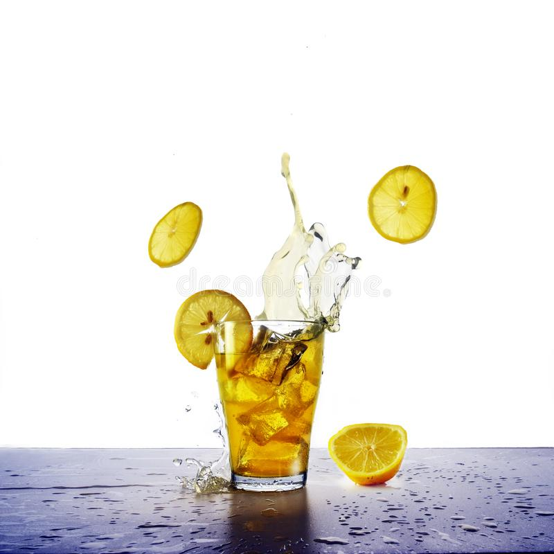Yellow drink with splash, ice cubes and flying lemons slices, re stock photography