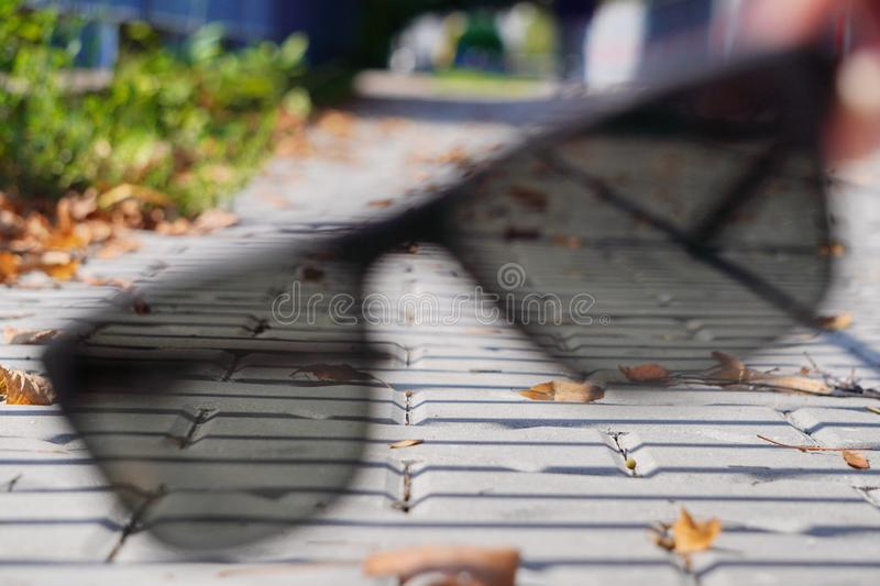 Yellow dry autumn leaves have fallen and lie on sidewalk. City street with sidewalk. Abstract symbol of autumn. close up, grey stock images