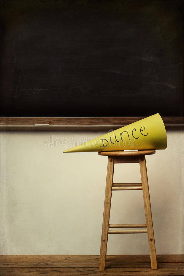 Yellow dunce hat on stool with chalkboard. In background royalty free stock photos