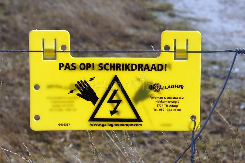 Yellow Dutch warning sign for a electric fence. royalty free stock photos