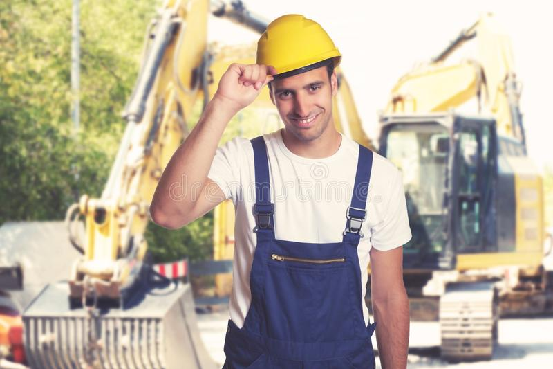 Yellow earthmover with handsome latin american construction work stock photography