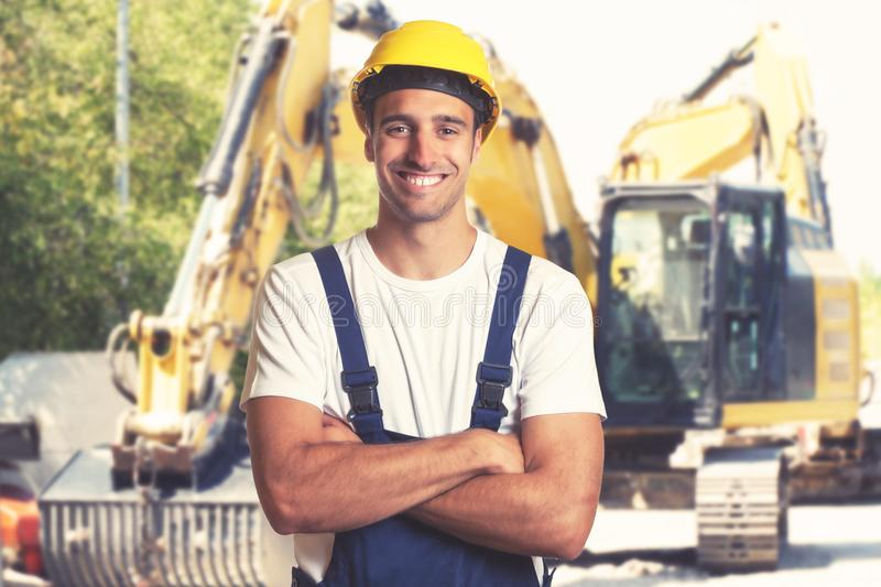 Yellow earthmover with strong latin american construction worker royalty free stock photo