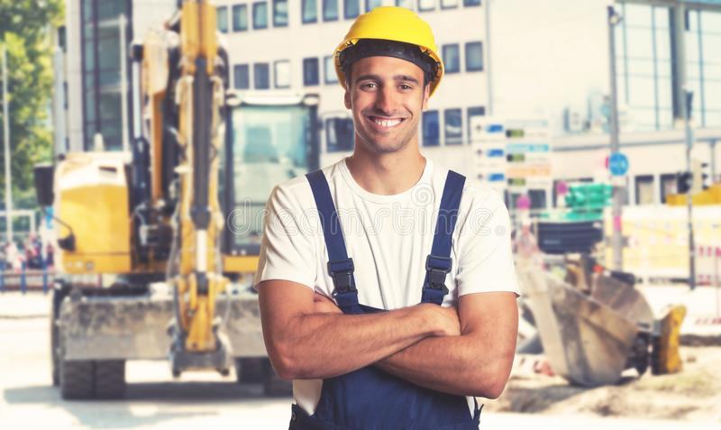 Yellow earthmover with strong latin american construction worker stock images