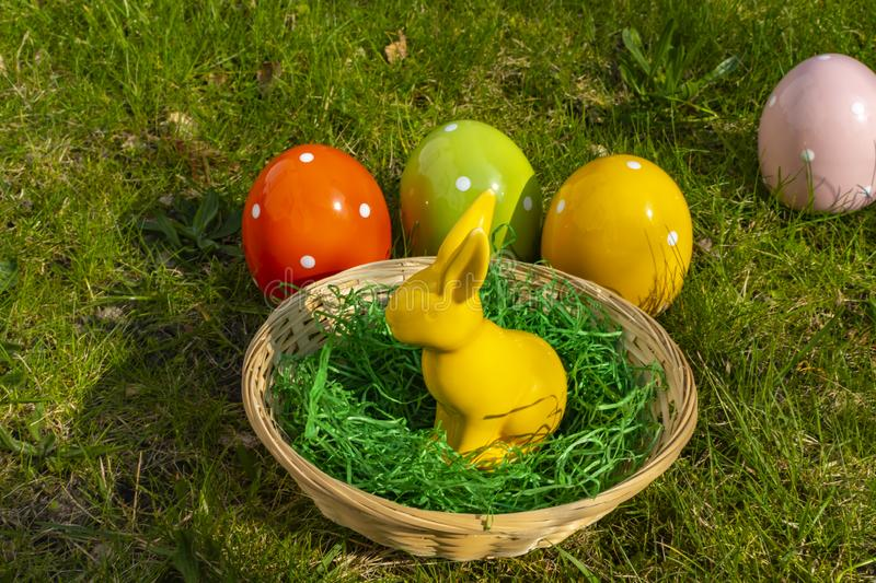 Yellow Easter bunny and colorful Easter eggs made of pottery with a basket on a meadow royalty free stock photos