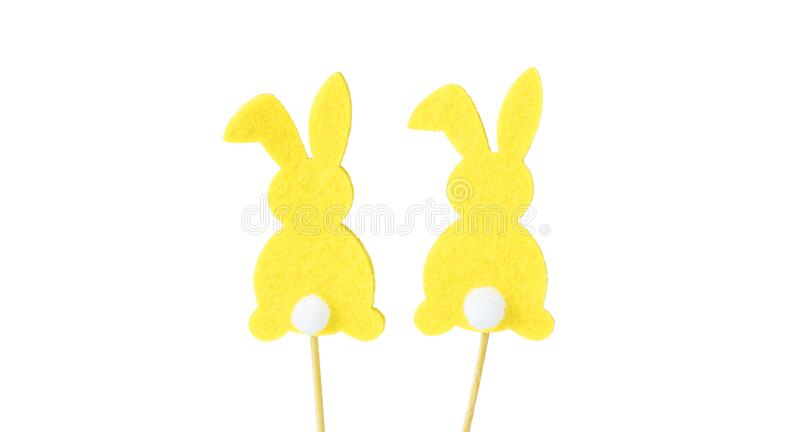 Yellow easter bunny rabbits with white tails, silhouette, on a wooden stick, isolated on a white background. Souvenir, decoration. For Easter. Easter concept royalty free stock images