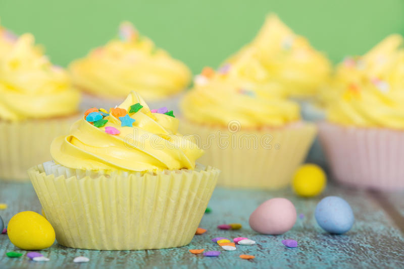 Yellow Easter cupcakes with candy and sprinkles royalty free stock photo