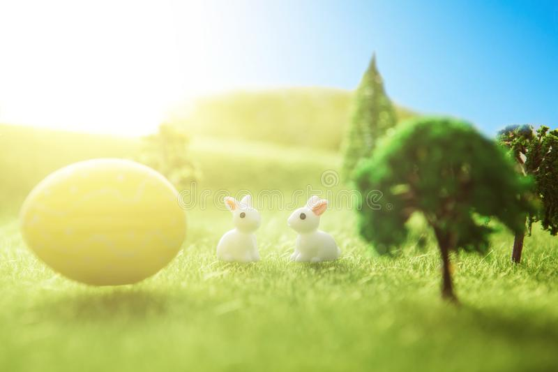 Yellow easter egg spring meadow with two white rabbit and easter eggs. Fairy tale stock photography