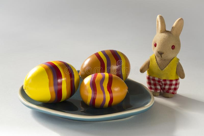 Yellow eggs on blue plate, with stuffed Easter bunny royalty free stock photos