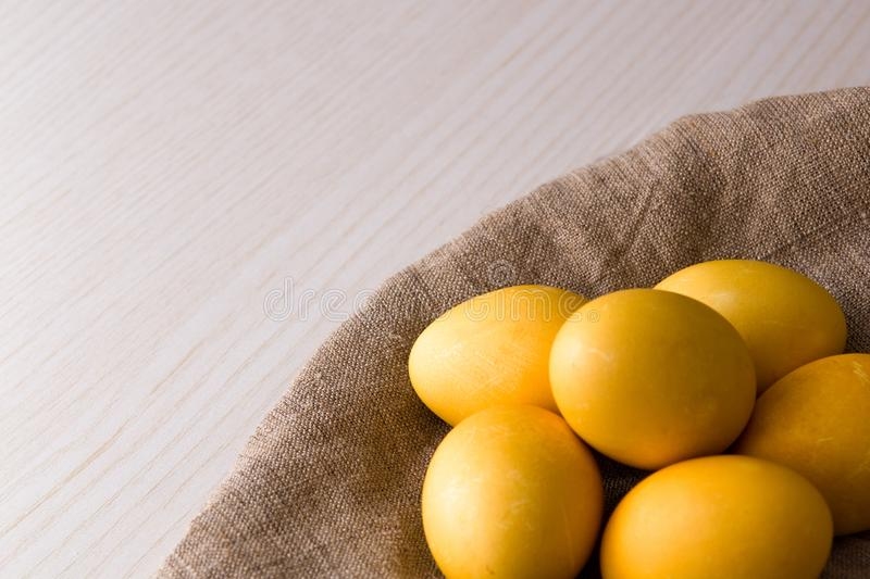 Yellow eggs on flax. Wooden light background, copy space, top view, easter background, sunlight, religious traditions, conept, close-up stock image