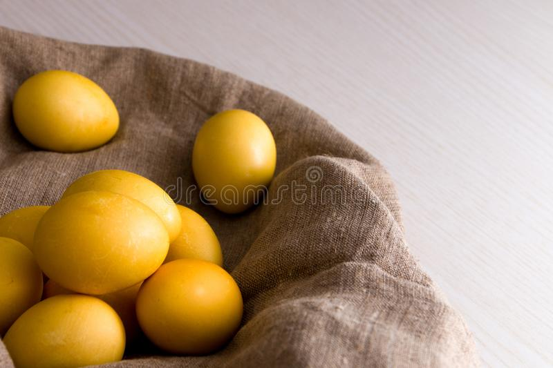 Yellow eggs on flax. Wooden light background, copy space, top view, easter background, sunlight, religious traditions, conept, close-up stock images