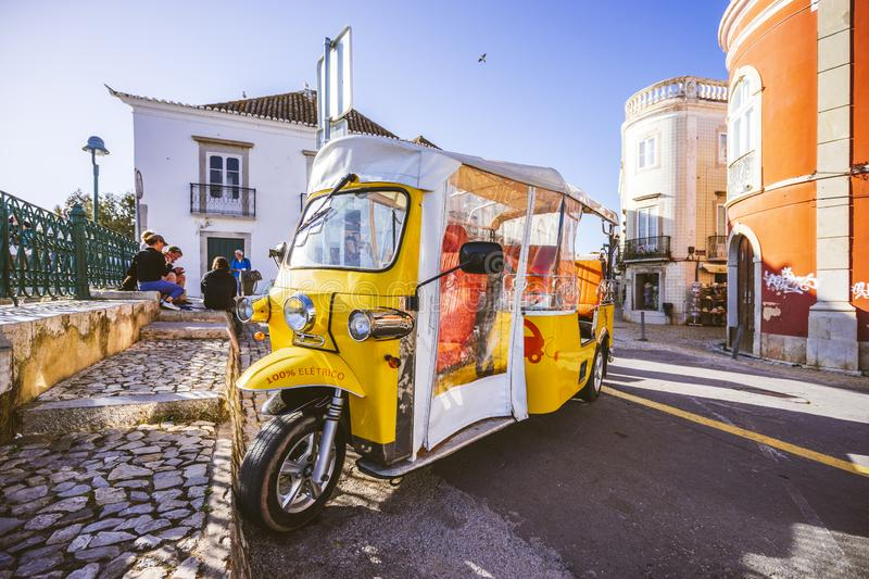 Yellow electric small vehicle for tourists on streets of Tavira, Algarve, Portugal royalty free stock photography