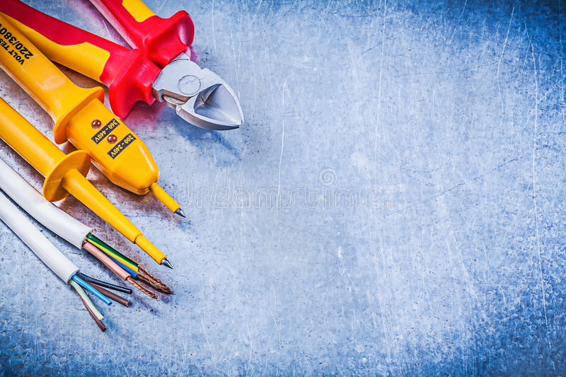 Yellow electrical tester wires nippers on metallic background co. Py space electricity concept royalty free stock photos