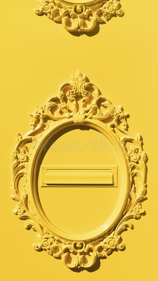 Yellow embellished metal gate door with mail slot, abstract solid color blast design. Vertical shot of ornate design of metal door, graphic resource, minimalist stock photo