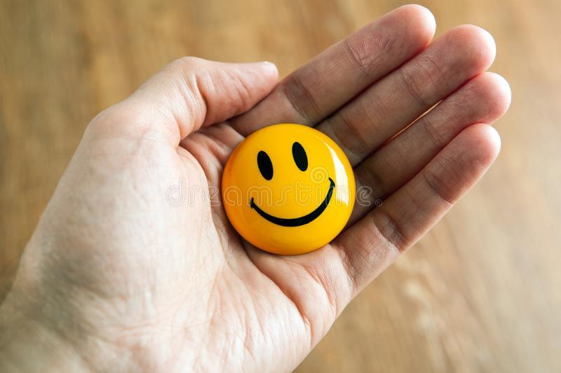Yellow emoticon icon in the hand. Close up royalty free stock photography