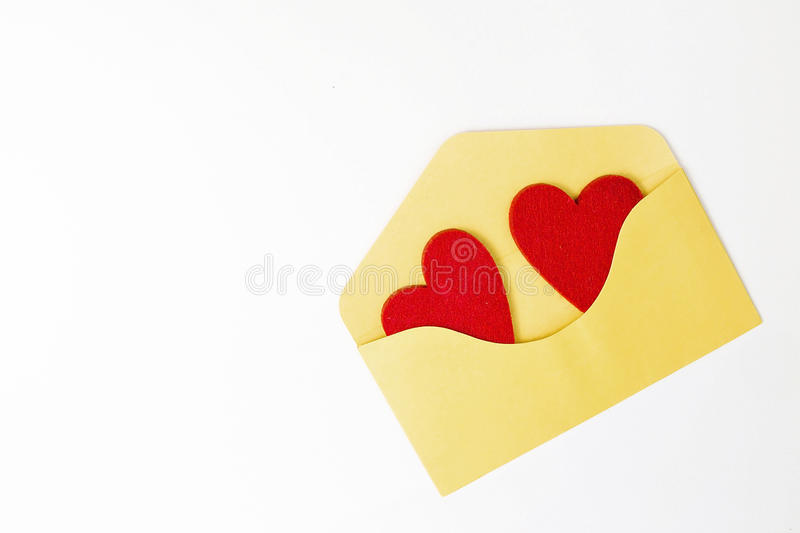 Yellow envelope and two felt red hearts in it on white table. Top view. Close up. Copy space. stock photography