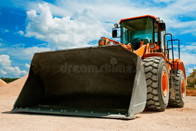 Yellow Excavator. On a construction site against blue sky royalty free stock photos