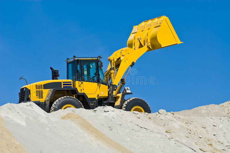 Yellow excavator. A yellow excavator working on sand, blue sky in the background