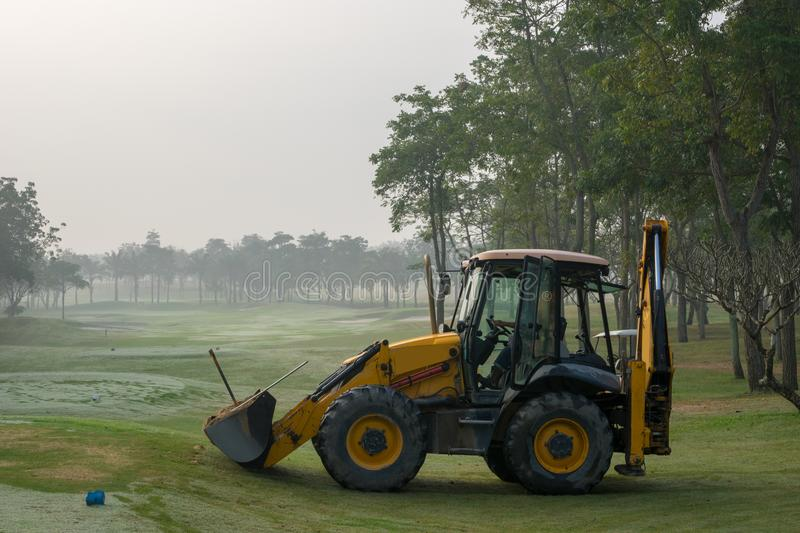 A yellow Excavator & x28;Back Hoe& x29; car working in golf court stock photography