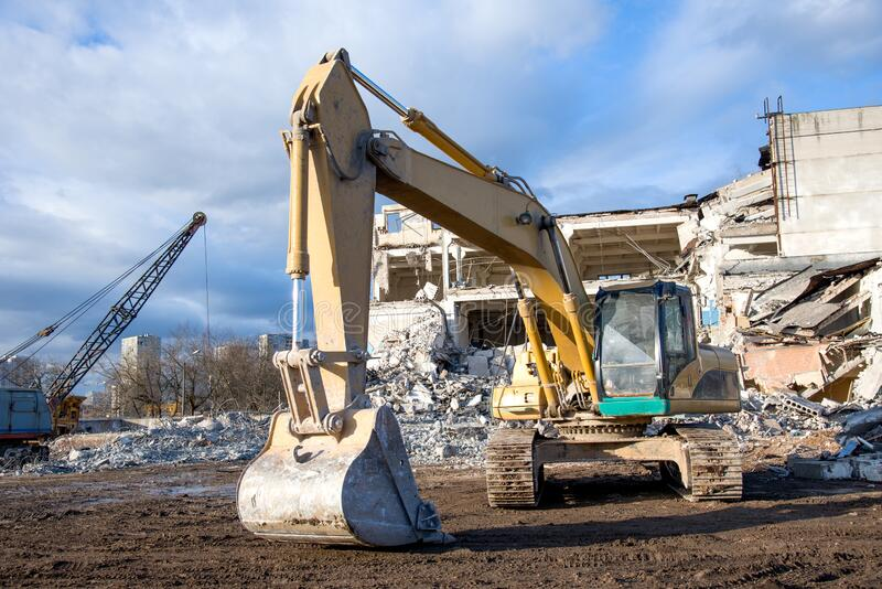 Yellow excavator with bucket at demolition of tall building. Hydraulic machine for demolish. Backhoe destroys concrete. Of the old structures on construction stock images