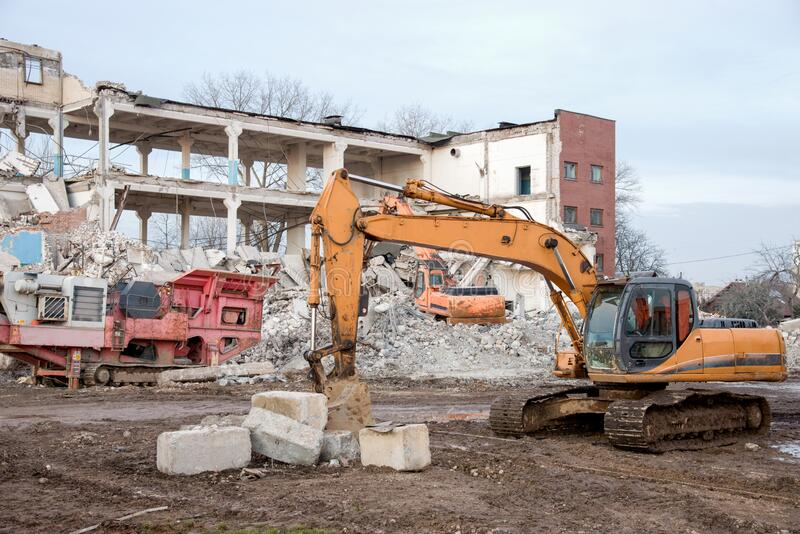 Yellow excavator with bucket at demolition of tall building. Hydraulic machine for demolish. Backhoe destroys concrete of the old. Structures on construction stock images