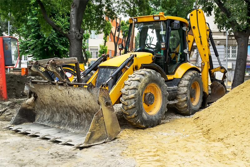 Yellow excavator with a bucket and large heap of sand at a road construction site on a city street on a summer day. royalty free stock photography