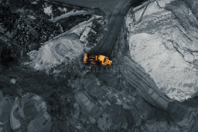 Yellow excavator or bulldozer in coal open cast mining quarry, industrial extraction of minerals, aerial top view. From drone stock image