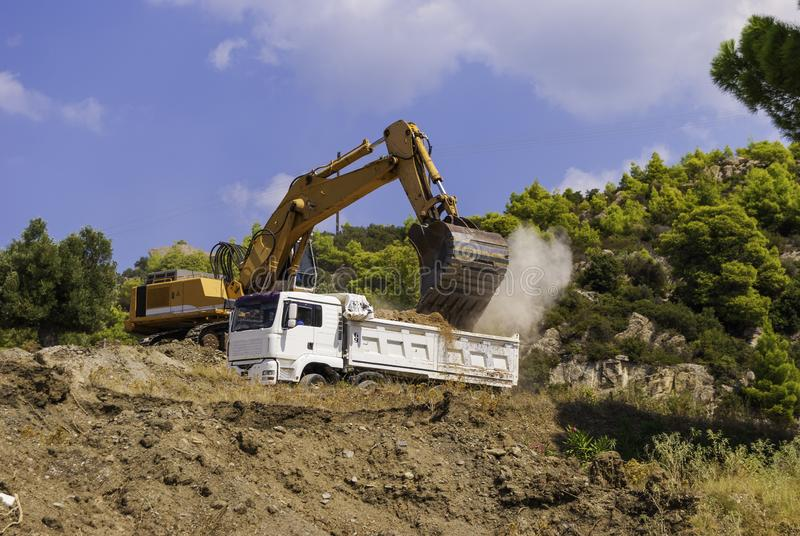 Yellow excavator on the construction site loads the soil into the body of a white dump truck royalty free stock photography