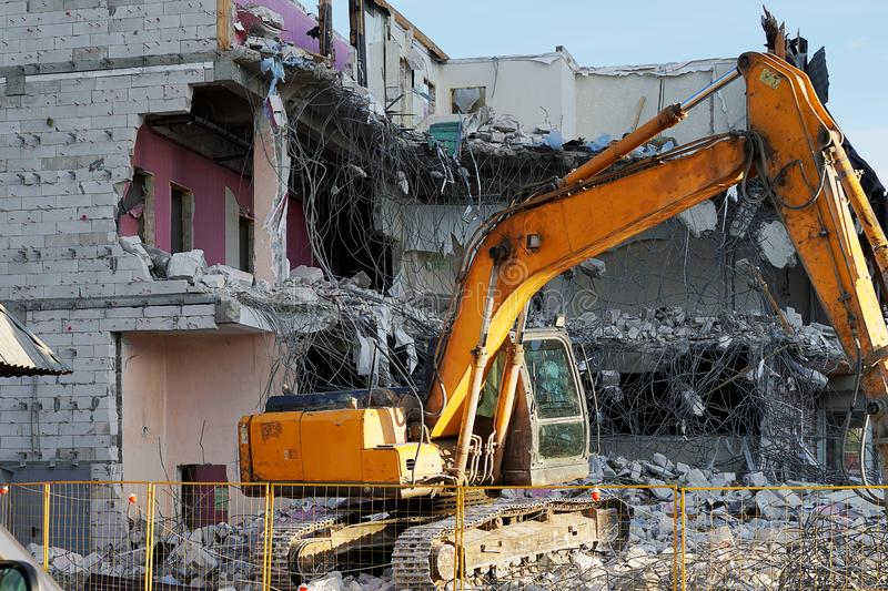 Yellow excavator demolishing a multi-storey building. Destroyed floors of the building, are pieces of stone, concrete, fittings. Construction equipment on stock images
