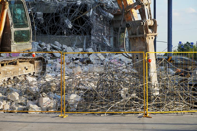 Yellow excavator destroyed multi-storey building tool. Lots of reinforcement, concrete and stones, red lights. The fence of the stock photos