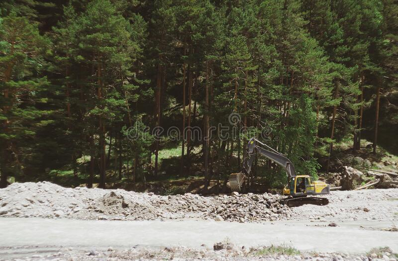 Yellow excavator. Directing the water of a mountain river royalty free stock image