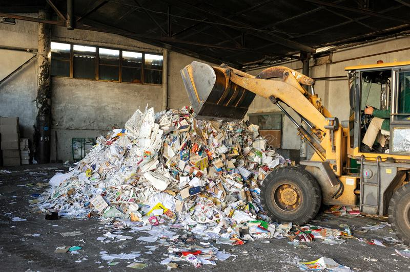 Excavator dumps cardboard garbage at waste recycling plant stock images