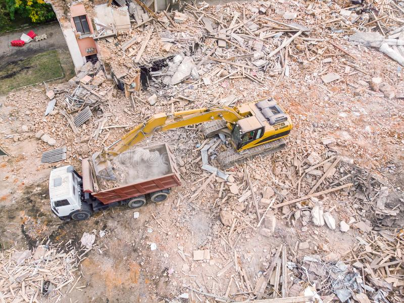 Yellow excavator loading a dump truck with debris and trash after building demolition. Aerial view royalty free stock image