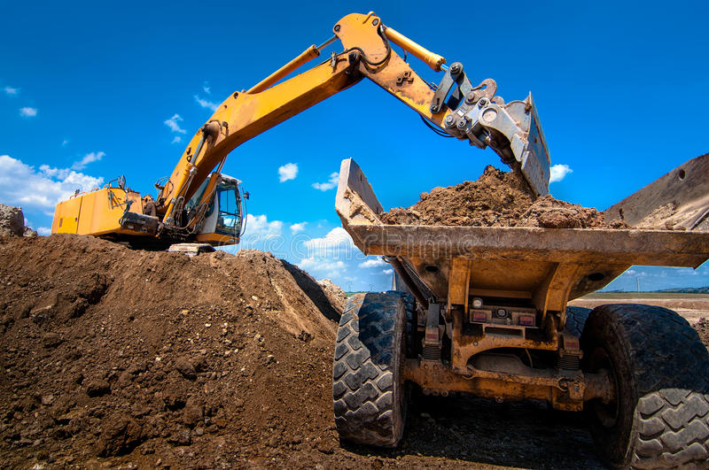 Yellow excavator loading soil into a dumper truck stock photos