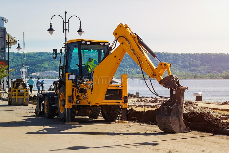 A yellow excavator with a lowered bucket stands at the site of the road construction work in a sea port on a sunny summer day royalty free stock photography