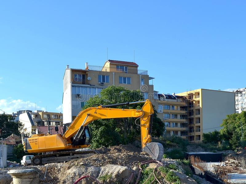 Yellow excavator at the site of road construction work near residential buildings stock photos