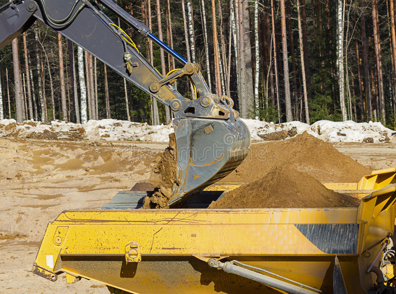 Yellow Excavator at Work. In forest stock images