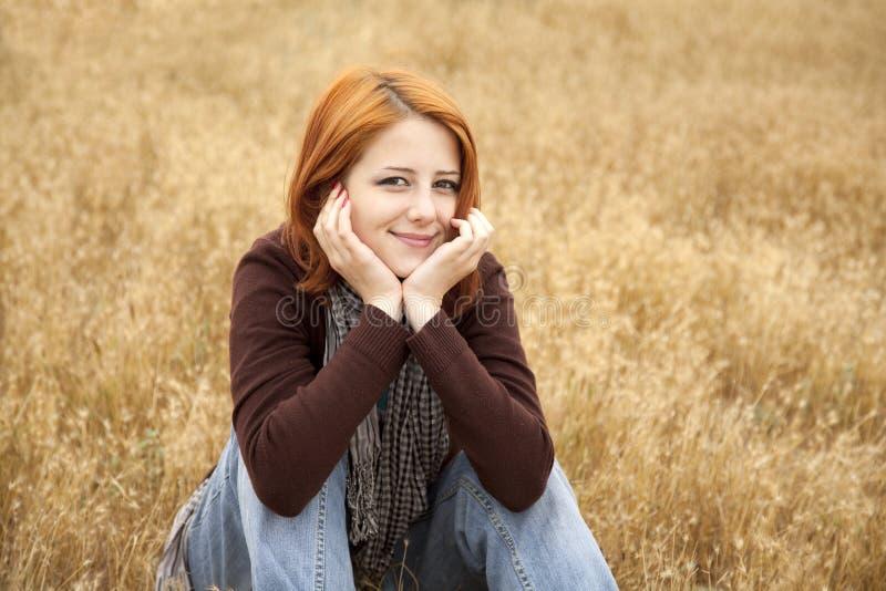 yellow för haired red för höstflickagräs sittande royaltyfri foto