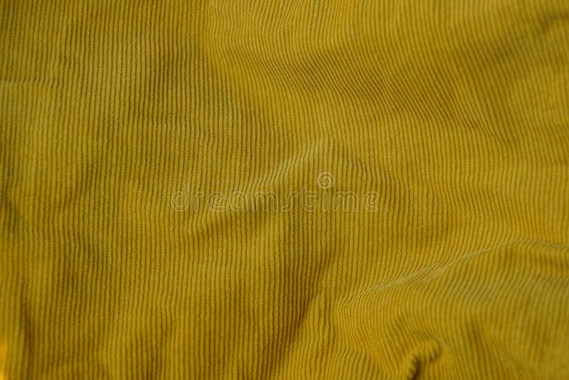 Yellow fabric texture from a crumpled piece of cloth on clothes. Yellow background of fabric from a crumpled piece of cloth on clothes stock photography