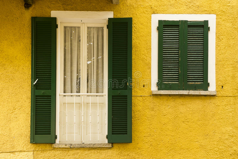 Yellow facade green shutters, Varenna, Italy stock images