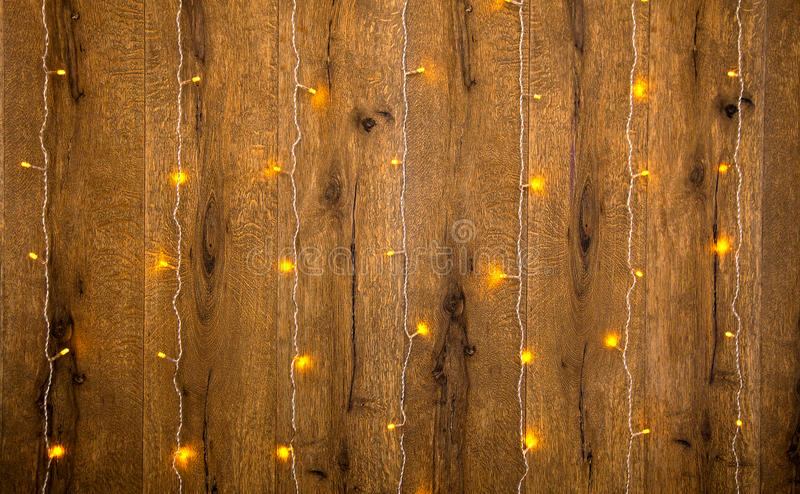 Yellow fairy lights on a wooden wall royalty free stock photography