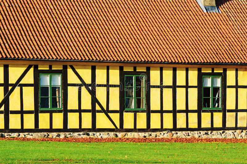 Yellow farmhouse. Bright yellow exterior of a farmhouse. Contrasting almost black wooden beams run across the facade. Orange roof tiles, dry leaves and green stock photography