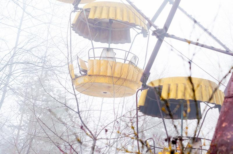 Yellow ferris wheel attraction in fog in abandoned amusement park overgrown with trees stock photos