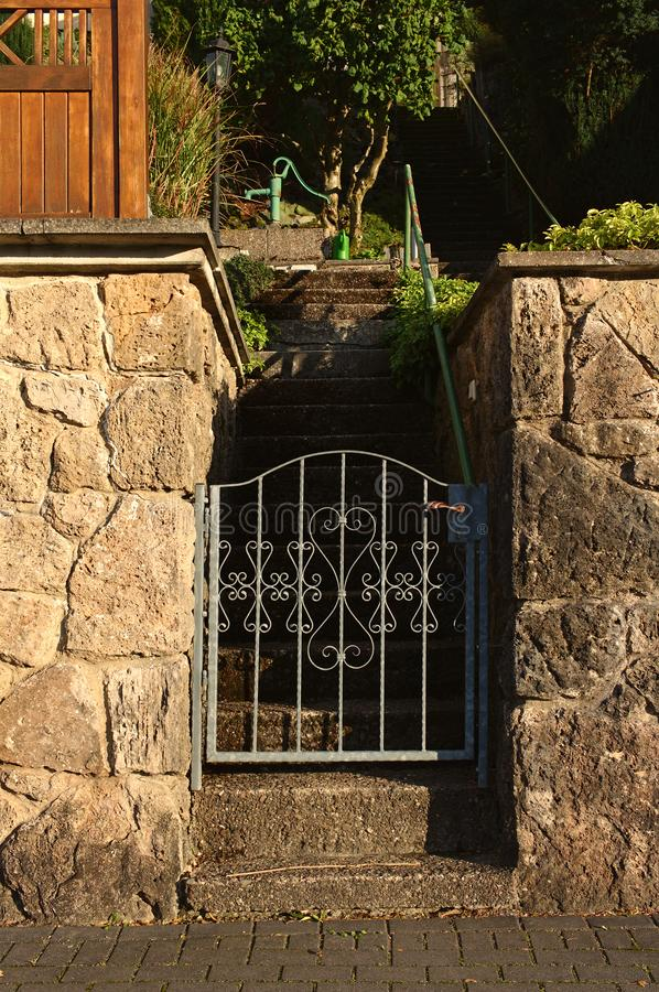 Yellow field stone wall lit by the evening sun with ornate iron gate that opens to a flight of stairs leading up into the garden stock images