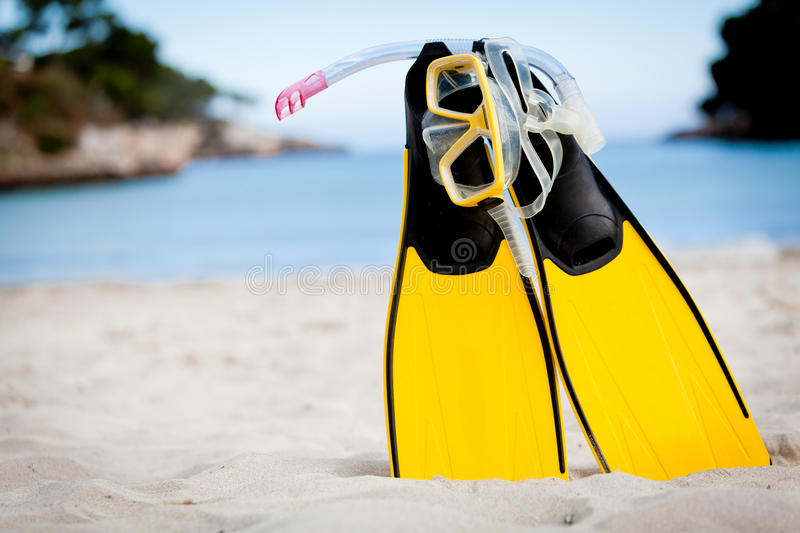 Yellow fins and snorkelling mask on beach in summer stock images