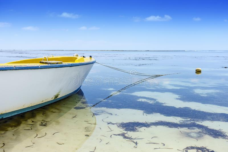 Yellow fisher boat anchoring on beach. Perspective view on yellow fisher boat anchoring on african beach, low tide, shallow depth of field royalty free stock images